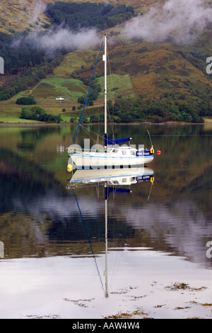 White sailing boat moored on Loch Leven near Ballachulish Glencoe with light clouds drifting by the mountainous - Stock Photo