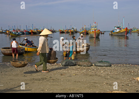 Woman in conical hat with pannier baskets passes old fashioned round woven boats Lang Chai fishing village near - Stock Photo