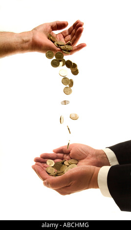 Pound coins falling from hand to hands - Stock Photo