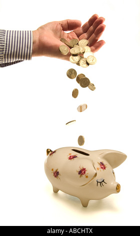 Pound coins falling from hand into piggy bank - Stock Photo