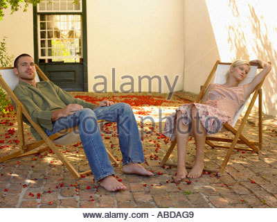 Couple sitting outdoors on deck chairs - Stock Photo