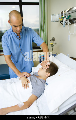 Boy lying in hospital bed, intern taking his temperature - Stock Photo