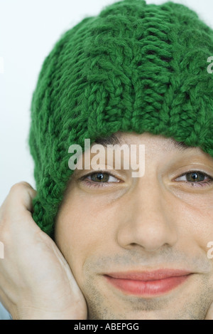 Young man pulling down knit hat over ears, portrait, close-up - Stock Photo