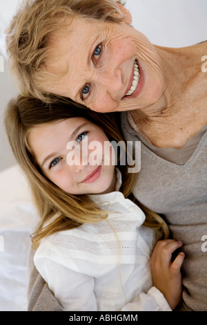 Senior woman and little girl smiling for the camera, indoors - Stock Photo