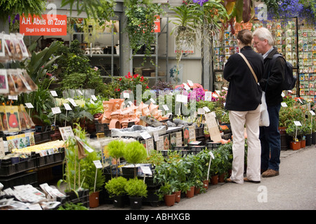 Couple at Flowermarket Bloemenmarkt rear view Singel Gracht Amsterdam Holland Netherlands - Stock Photo