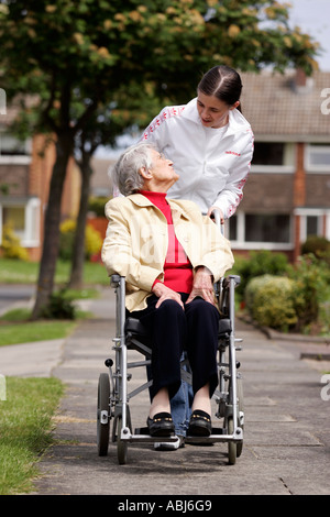 teenager helping old lady in wheel chair - Stock Photo