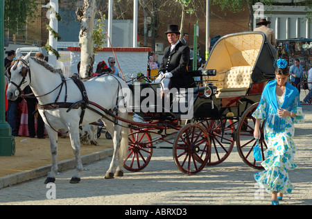 Carriage and horses and a girl in a flamenco dress April Fair Seville Andalusia Spain - Stock Photo