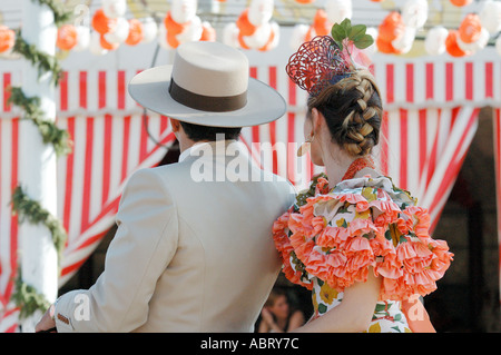 Young man with a girl in a flamenco dress riding pillion at the April Fair Seville Andalusia Spain - Stock Photo