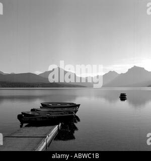 Black and white image of boats on a lake with mountains in the background. - Stock Photo