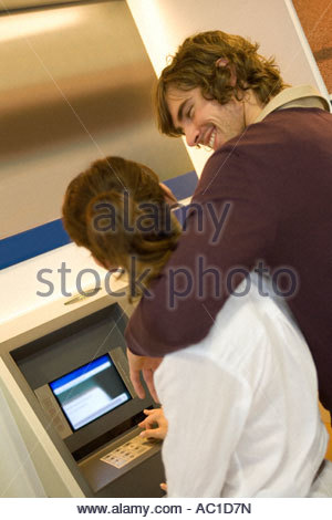 A couple at an ATM machine - Stock Photo