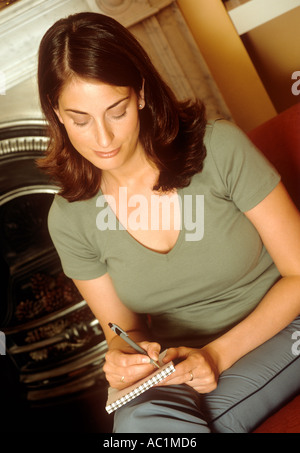 Woman sitting writing in a notebook - Stock Photo