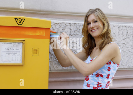 young woman in front of a letterbox, Austria - Stock Photo