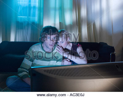 A couple watching a horror movie - Stock Photo