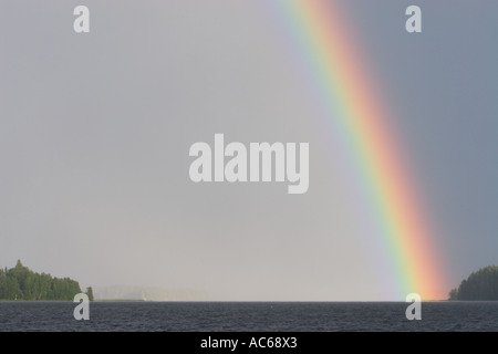 The end of the rainbow hitting spit of land in a lake , Finland - Stock Photo