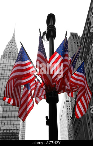 Stars and stripes american flags on lamppost lamp post with Empire State Building midtown Manhattan New York City - Stock Photo