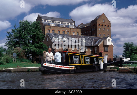 Three people aboard narrowboat working through Coxes Lock on River Wey Navigation, Addlestone, Surrey, England - Stock Photo