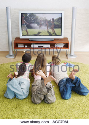 Three young kids watching television - Stock Photo