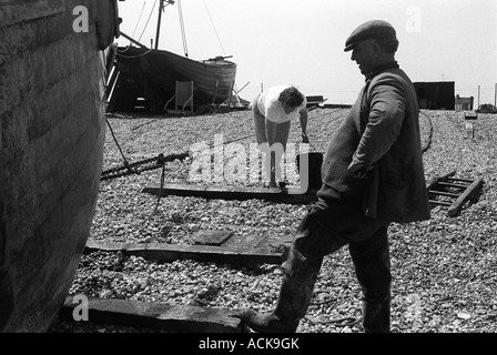 Fisherman and wife Dungeness Kent 1969. Woman painting creosote  onto wooden runners. - Stock Photo