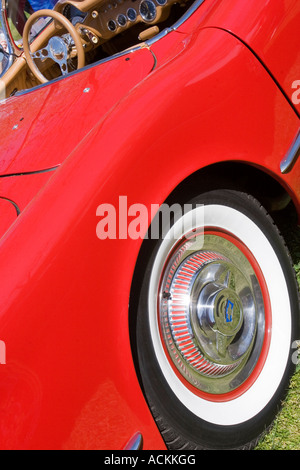 Rear wheel and steering wheel of a bright red 1954 Chevrolet Corvette convertible classic car at an auto show - Stock Photo