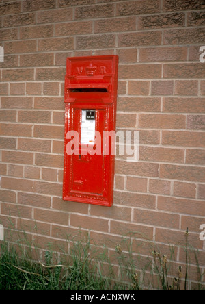 Red Victoria Regina Royal Mail postbox in brick wall - Stock Photo