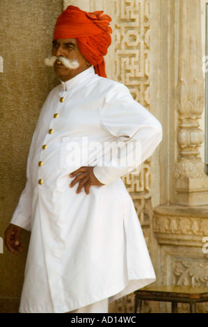 Vertical portrait of traditionally dressed Rajasthani man in a pristine white tunic and red turban. - Stock Photo