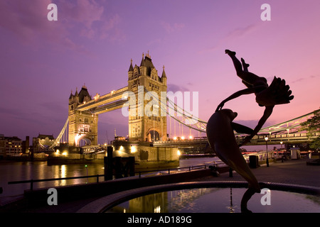 Tower Bridge and 'Girl with a Dolphin' fountain statue at dusk, London, England - Stock Photo