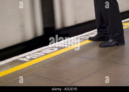 Young businessman stands on London Underground platform as tube train enters station - Stock Photo