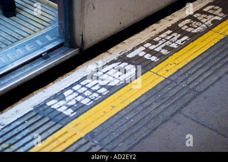 Open tube train door on London Underground platform with mind the gap sign on platform floor - Stock Photo