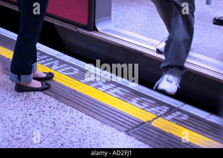 Young man steps off tube train on London Underground platform - Stock Photo