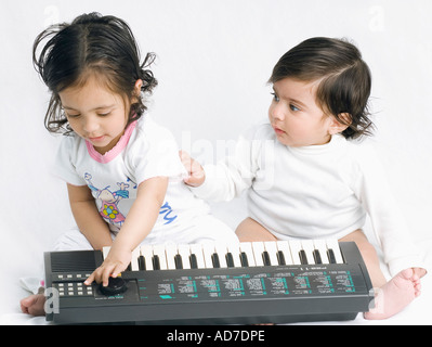 Close-up of a baby girl playing an electronic piano with her brother sitting beside her - Stock Photo
