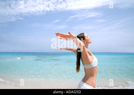 Beach wellness young woman doing a yoga excercise - Stock Photo