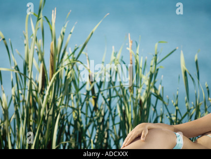 Woman in bikini lying on side with hand on hip, cropped view - Stock Photo
