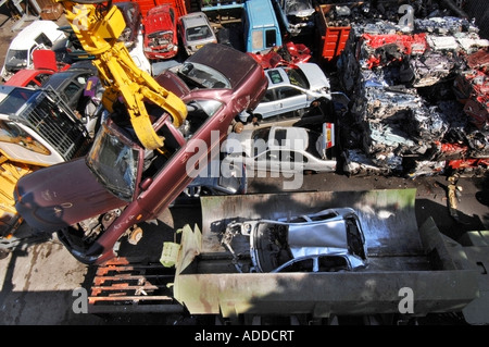 A crane lifts a car over crushed vehicles at a car recycling and salvage yard - Stock Photo