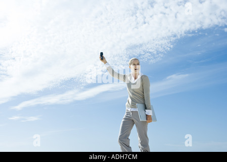 Woman holding laptop under arm, holding up cell phone, laughing - Stock Photo
