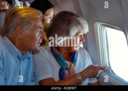 Seniorenpaar im Flugzeug aus dem Fenster schauend - Stock Photo