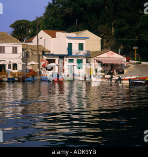 Quayside bars with chairs sun umbrellas and colourful boats moored at Logos on Paxos Island The Greek Islands Greece - Stock Photo