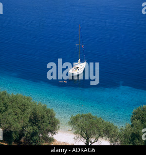 View along tree lined coast into a bay where a yacht is moored with woman swimming near in Kioni Bay Ithaca Greek - Stock Photo