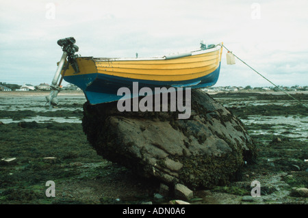Small boat left high and dry on top of a boulder by receding tide Jersey Channel Islands UK - Stock Photo