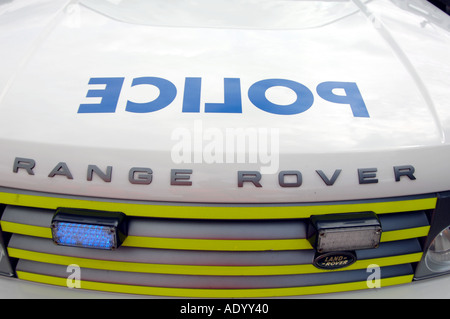 Police sign on Range Rover car bonnet, backwards for mirror reflection. Blue flashing lights in grill - Stock Photo