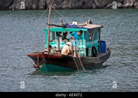 Hauling in nets on small fishing boat Halong Bay Vietnam - Stock Photo
