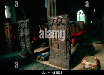 Ornate ancient wooden carved pews and tapestry kneeling pads St Keverne Parish Church Cornwall England - Stock Photo