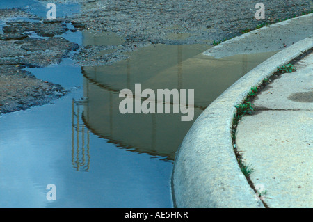 Neighborhood water tower reflecting in puddle on street by curved sidewalk - Stock Photo