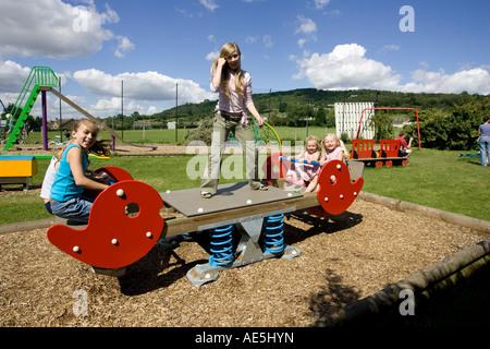 Children playing on seesaw in local playground Woodmancote UK - Stock Photo