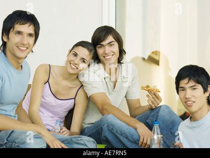 Young adult friends hanging out and eating together - Stock Photo
