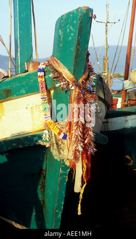 Prow of traditional Cham fishing boat adorned with garlands and scarves on the Sanke river, Kampot, Cambodia - Stock Photo