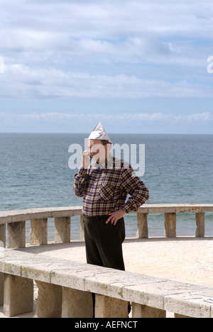 A portuguise man with paper hat answers his mobile phone whilst on a jetty in Albufera Portugal - Stock Photo