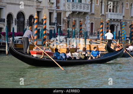 Gondoliers rowing group of Japanese tourists in gondola on the Grand Canal Venice Italy - Stock Photo