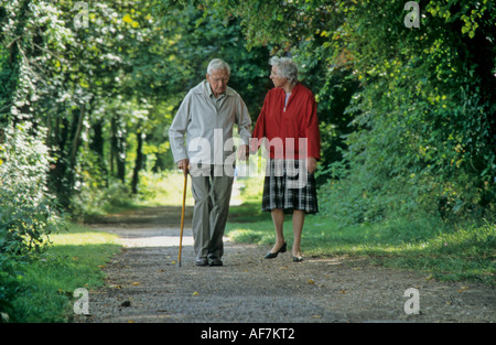elderly couple enjoying a leisurely walk along Chichester Canal towpath in the shade of woodland trees - Stock Photo