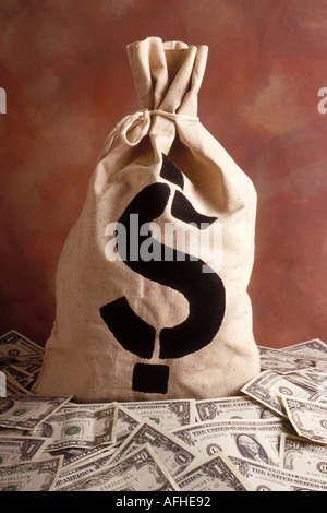 A money sack or bag with a US dollar sign on it sitting on a pile on American currency - Stock Photo