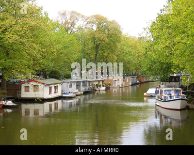 Canal boats in tree lined Amsterdam canal Netherlands - Stock Photo